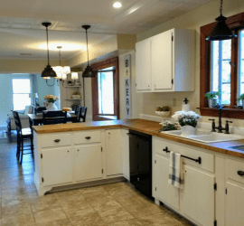 Farmhouse kitchen remodel on a budget with painted white cabinets, butcher block countertops, recessed and pendant lighting and oil rubbed bronze bridge faucet. Lots of budget remodeling ideas and inspiration. #kitchenremodel #farmhouse