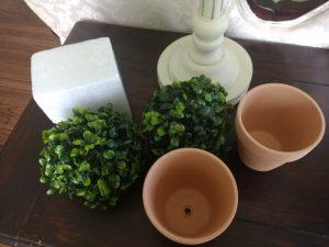 Terracotta pots, boxwood balls, and floral foam