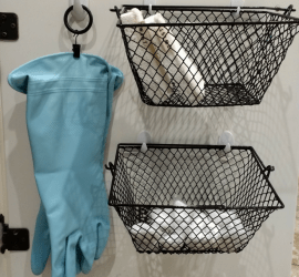 Ideas for organizing under the kitchen sink. Curtain ring clip and command hooks used to hang dish washing gloves. Command hooks and dollar tree baskets used to store sponges and dish washing tablets.