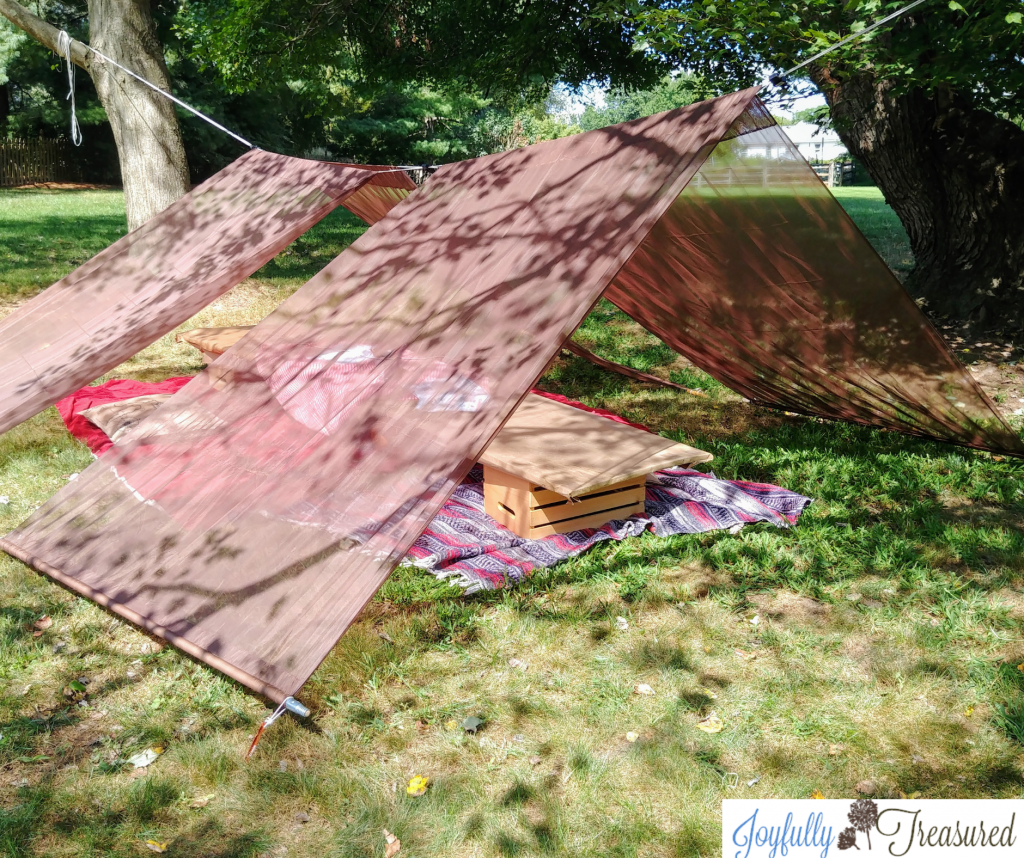 Make a DIY tent with clothesline and curtains, perfect for a camping themed birthday party!