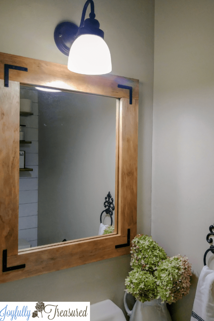 1960's sheet mirror turned farmhouse bathroom mirror. $100 room challenge. 1960's bathroom makeover with a $100 budget. Farmhouse style powder room makeover on a budget. #budgetdecor #homediy #farmhousestyle #beforeandafter #budgetreno #farmhousebathroom