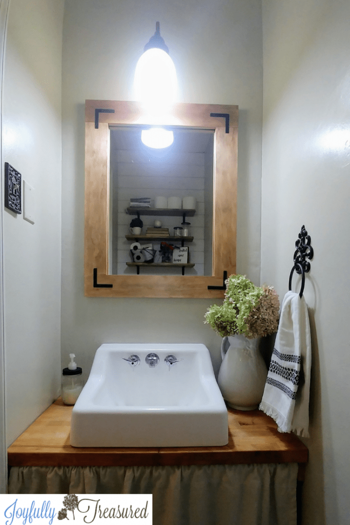 DIY wood frame mirror, Industrial farmhouse bathroom mirror with corner L brackets for a $100 bathroom makeover. We took our 1960s powder room and updated it to farmhouse style with just a $100 budget. Lots of great ideas for budget bathroom decor. #budgetdecor #homediy #bathroomdecor #farmhousedecor #farmhousestyle #bathroomideas #rustic